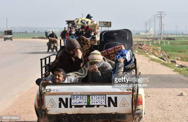 TOPSHOT Civilians fleeing the city of Afrin in northern Syria are seen on the back of a pick up truck as they enter the town of Tal Rifaat in the...
