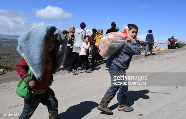 TOPSHOT Civilians fleeing the city of Afrin in northern Syria walk at the mountainous road of alAhlam while heading towards the check point in...