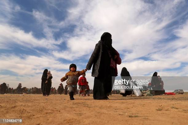 Civilians fleeing the Islamic State's group embattled holdout of Baghouz gather in a field on February 13, 2019 during an operation by the US-backed...