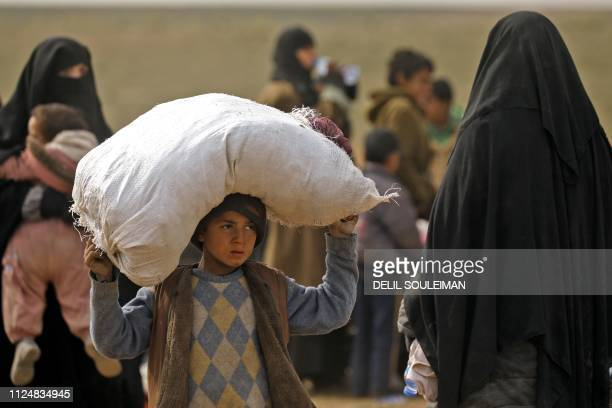 Civilians fleeing the Islamic State's group embattled holdout of Baghouz gather in a field on February 13 2019 during an operation by the USbacked...