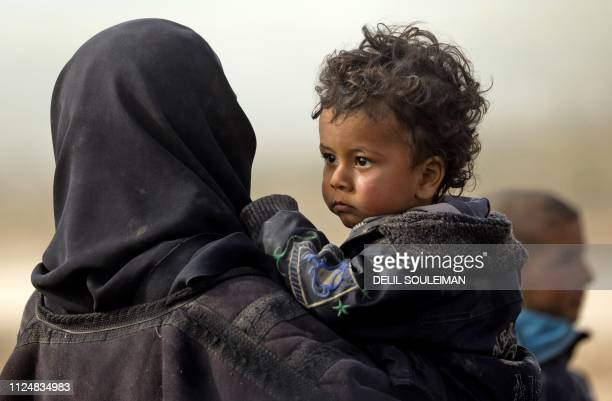 Civilians fleeing the Islamic State's group embattled holdout of Baghouz stand in a field on February 13, 2019 during an operation by the US-backed...