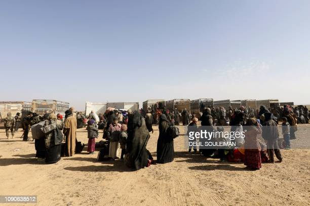 Civilians gather at an Syrian Democratic Forces outpost near the frontline village of Baghouz near the Iraqi border on January 26 ahead of being...