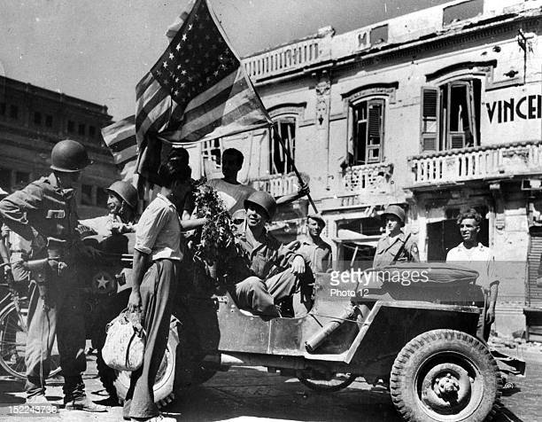 Civilians give gift of flowers and wave flags as american vehicles arrive in Messina August 24 1943