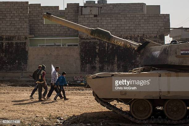 Civilians hold a white flag as they pass an Iraqi Army Armoured Ninth Division tank on the frontline in the Intisar neighbourhood on November 13 2016...