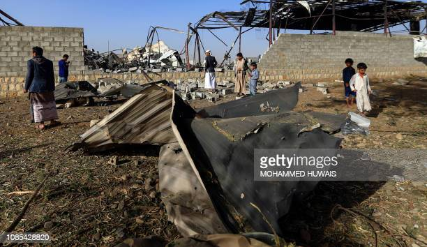 Civilians inspect the damage at a factory after a reported airstrike by Saudiled coalition in the Yemeni capital Sanaa on January 20 2019 Coalition...