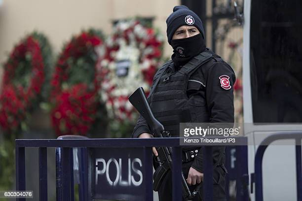 Civilians lay flowers on the gates at the entrance of the Russian Consulate while police and soldiers make their rounds on December 20 2016 in...
