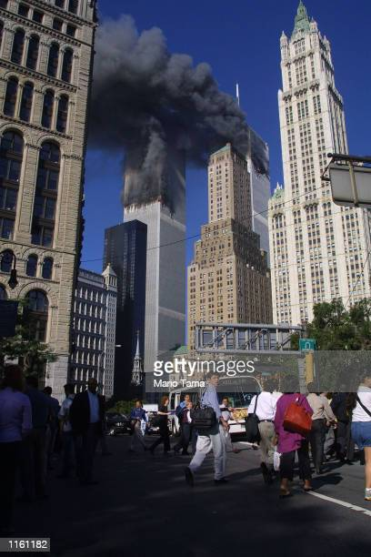 Civilians leave the area as a tower of the World Trade Center burn September 11 2001 after two airplanes slammed into the twin towers in an alleged...