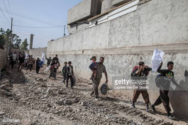 Civilians leave their homes under the protection of soldiers with Iraqi Special Operations Forces 1 during their operation to retake Mosul and nearby...