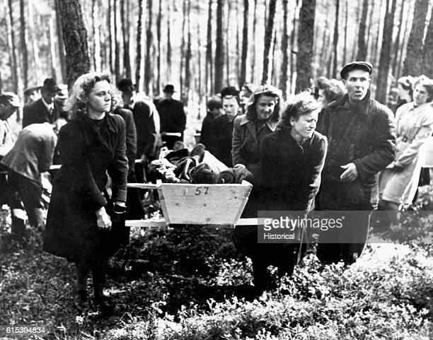 Civilians of Neunburg bear victims of SS killings to burial ground, after bodies were exhumed from mass grave where their murderers had dumped them....