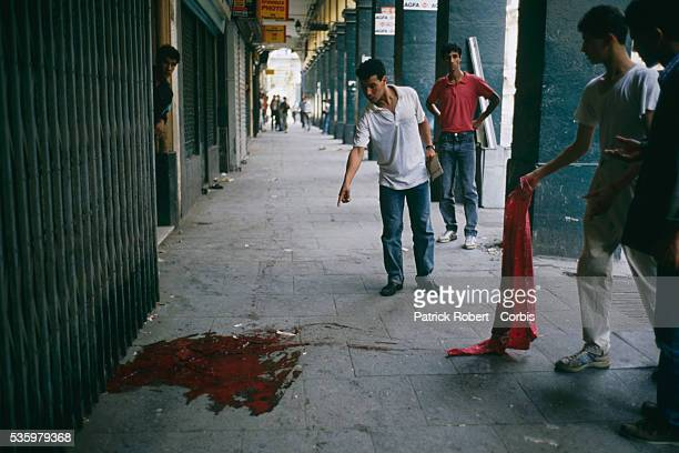 Civilians point to a pool of blood on the streets of Algiers after riots broke out instigated by rising food prices in a country with an unemployment...