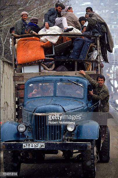 Civilians riding atop truck filled with their belongings while fleeing from a frontline neighborhood where fighting between govt HezbiIslami forces...
