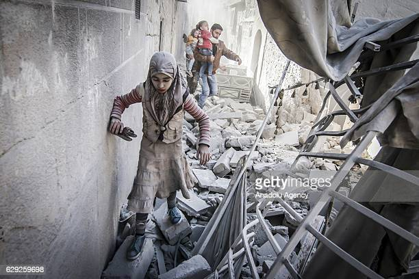 Civilians run around the debris of damaged buildings after the war crafts belonging to the Assad Regime's and Russian forces' airstrikes over...