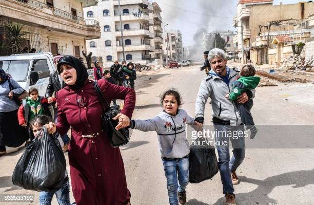 TOPSHOT Civilians run for cover from explosions in the city of Afrin in northern Syria on March 18 after Turkish forces and their rebel allies took...