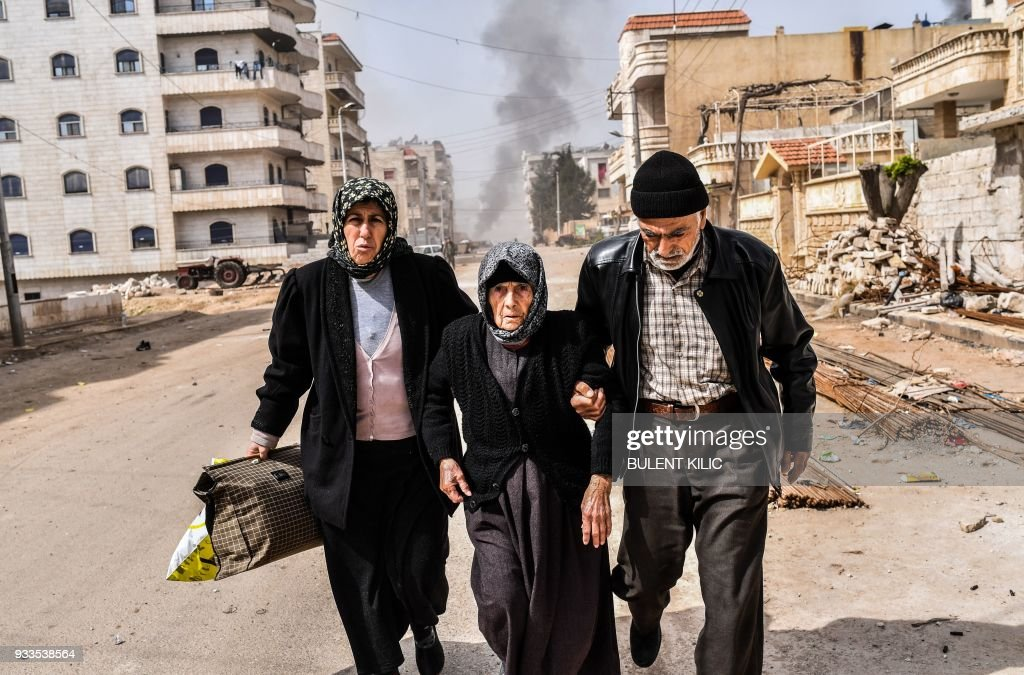 Civilians run for cover from explosions in the city of Afrin in northern Syria on March 18, 2018, after Turkish forces and their rebel allies took control of the Kurdish-majority city. Turkish-backed rebels have seized the centre of Afrin city in northern Syria, Ankara said, as they made rapid gains in their campaign against Kurdish forces. A civilian inside Afrin said that rebels had deployed in the city centre and that the Kurdish People's Protection Units (YPG) militia had withdrawn. /