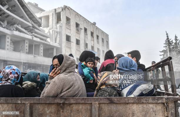 TOPSHOT Civilians sit in the back of a truck as they flee the city of Afrin in northern Syria on March 18 after Turkish forces and their rebel allies...