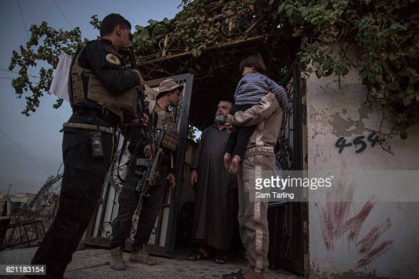 Civilians speak with Iraqi Special Forces as they advance through the neighborhood of Tahrir and Zahara, formerly named after Saddam Hussein, on the...