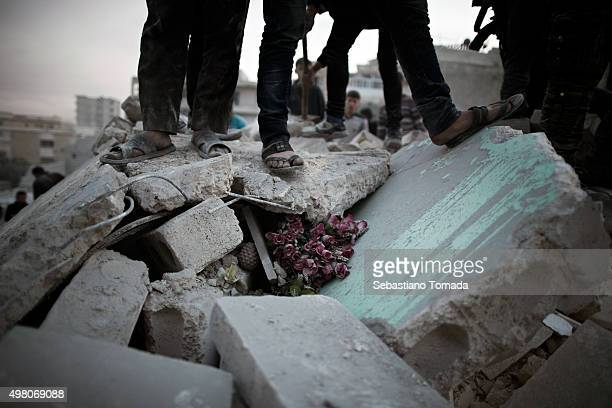 Civilians stand on top of the remaining of a residential building in Aleppo Syria as they look for survivors March 20 2013