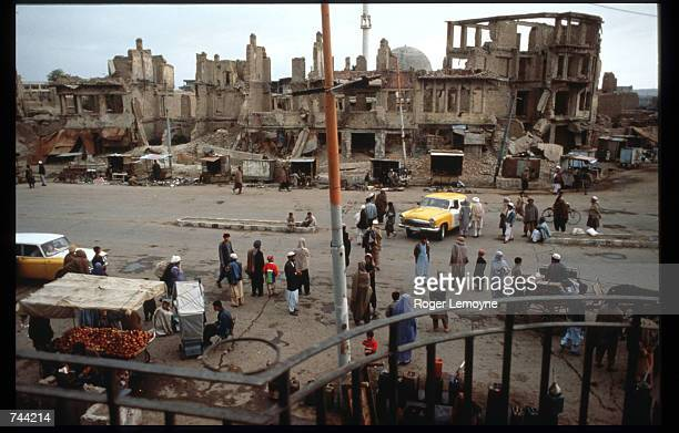 Civilians visit a market across from ruined buildings October 21, 1996 in Kabul, Afghanistan. The Taliban army faces opposition by the guerrillas of...