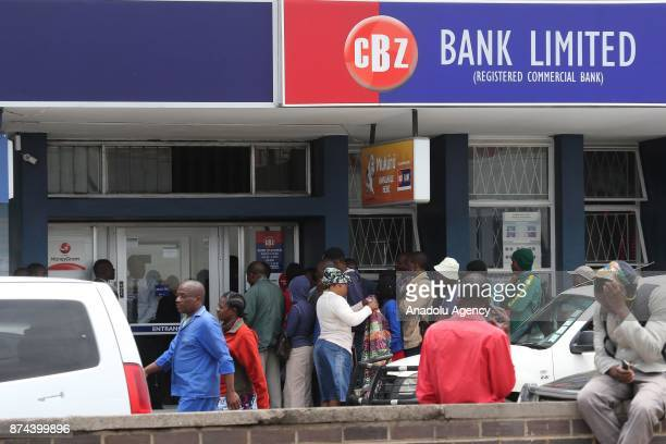 Civilians wait in a queue to withdraw their money from a bank's ATM as the soldiers seal off a main road to the presidential office within the...