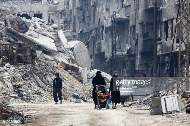 Civilians walk along a destroyed street in the former rebelheld town of Harasta in Eastern Ghouta on March 30 a week after regime forces retook the...