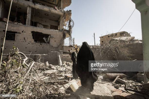 Civilians walks up through city ruins while fleeing fighting in Islamic state controlled area. More than a thousand dead and a city in ruins. The...