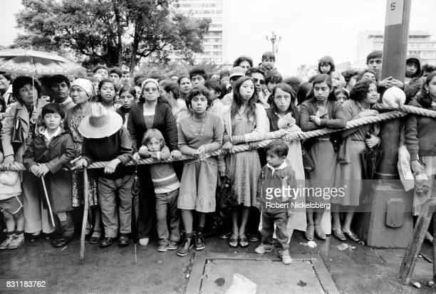 Civilians watch as President Efraín Rios Montt arrives for a ceremony at the Presidential Palace October 20 1982 in Guatemala City Guatemala...