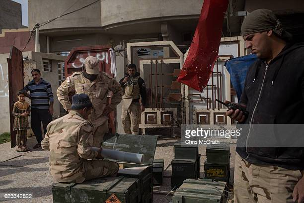 Civilians watch on from in front of their house as Iraqi Army Armoured Ninth Division soldiers check their equipment in the Entisar neighborhood on...