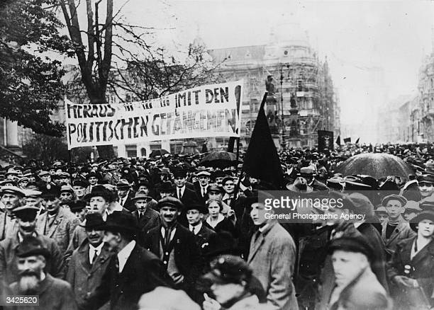 Civilians waving a banner at a political demonstrations in postwar Germany The banner reads 'Out with the Political Prisoners'