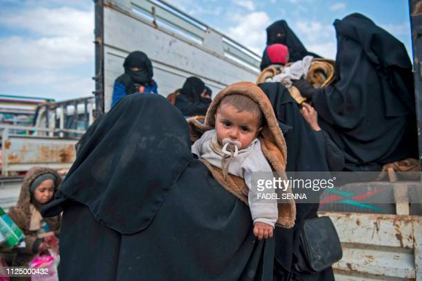 Civilians who fled from the embattled Baghouz area in the eastern Syrian province of Deir Ezzor sit in a truck on February 14 2019 during an...