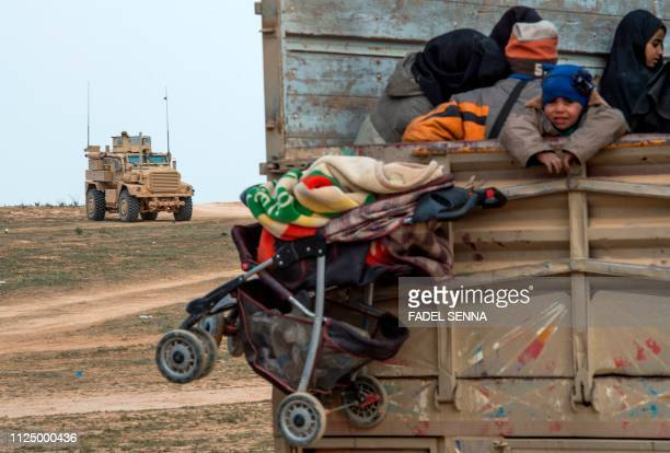 Civilians who fled from the embattled Baghouz area in the eastern Syrian province of Deir Ezzor sit in a truck on February 14, 2019 during an...