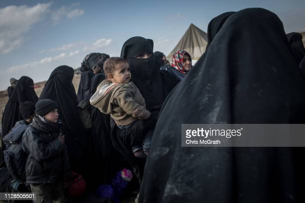 Civilians who have fled fighting in Bagouz board trucks after being screened by members of the Syrian Democratic Forces at a makeshift screening...