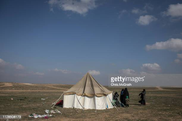 Civilians who have fled fighting in Bagouz wait to board trucks after being screened by members of the Syrian Democratic Forces at a makeshift...