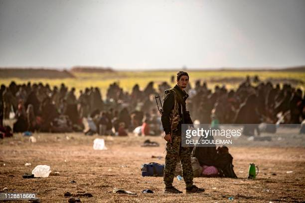 Civilians who streamed out of the Islamic State group's last Syrian stronghold sit at a screening point for new arrivals run by USbacked Syrian...