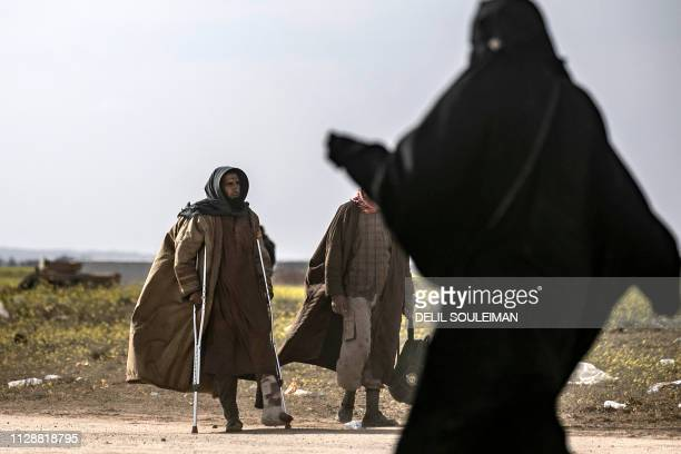 Civilians who streamed out of the Islamic State group's last Syrian stronghold walk towards a screening point for new arrivals run by US-backed...