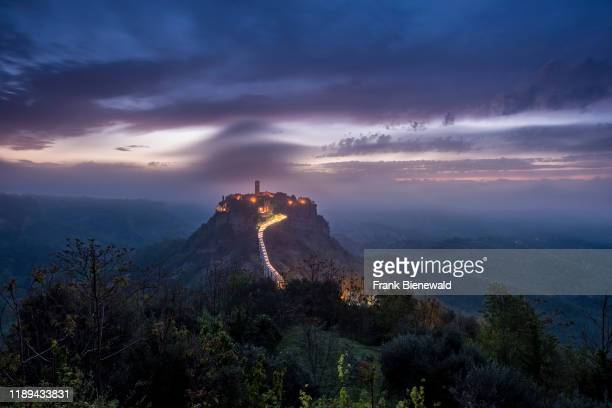 Civita di Bagnoregio, an old etruscan settlement, located on top of a volcanic tuff plateau, illuminated at night before sunrise.