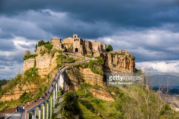 Civita di Bagnoregio an old etruscan settlement located on top of a volcanic tuff plateau illuminated by the setting sun dark thunderstorm clouds in...