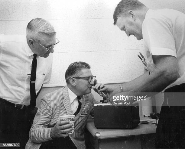 Civitan Club member drink in hand is given breathalyzer test by police Left to right are Spencer Garrett Aurora chief of police Lou Cohn the club...