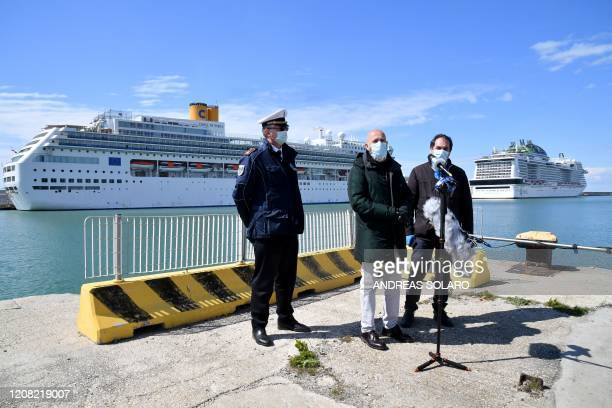 Civitavecchia mayor Ernesto Tedesco and vice mayor Massimiliano Grasso stand by a municipal police oficer as they address the media by Italy's Costa...