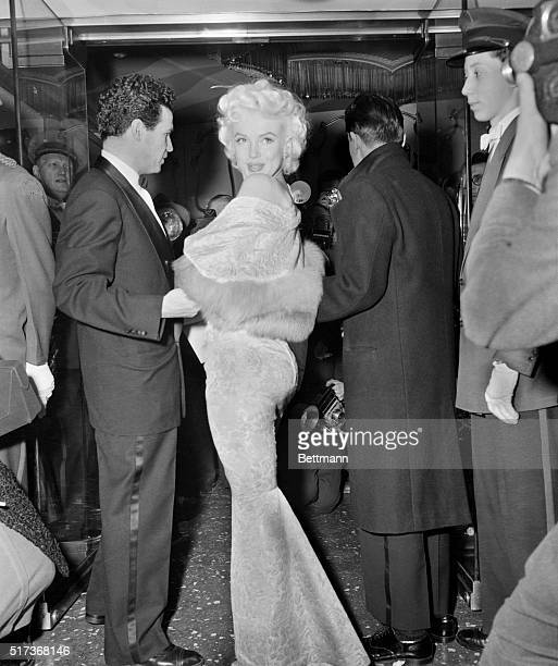 Clad in a tightlyfitted gown Marilyn Monroe glances over her shoulders on arriving at the Astor Theatre tonight for the benefit premiere of 'East of...