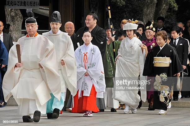 Clad in formal kimono Mongolianborn sumo grand champion or yokozuna Hakuho and his bride Sayoko are led by Shinto priests for their wedding ceremony...