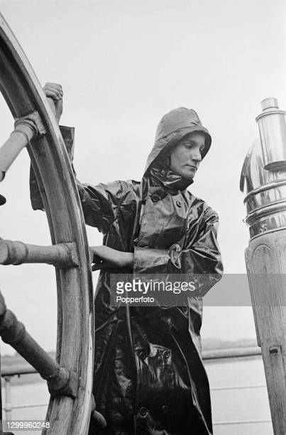 Clad in oilskins and sou'wester rain hat, trainee Merchant Navy bosun Robin Alway Hall takes a turn at the wheel on the deck of the Training Ship...