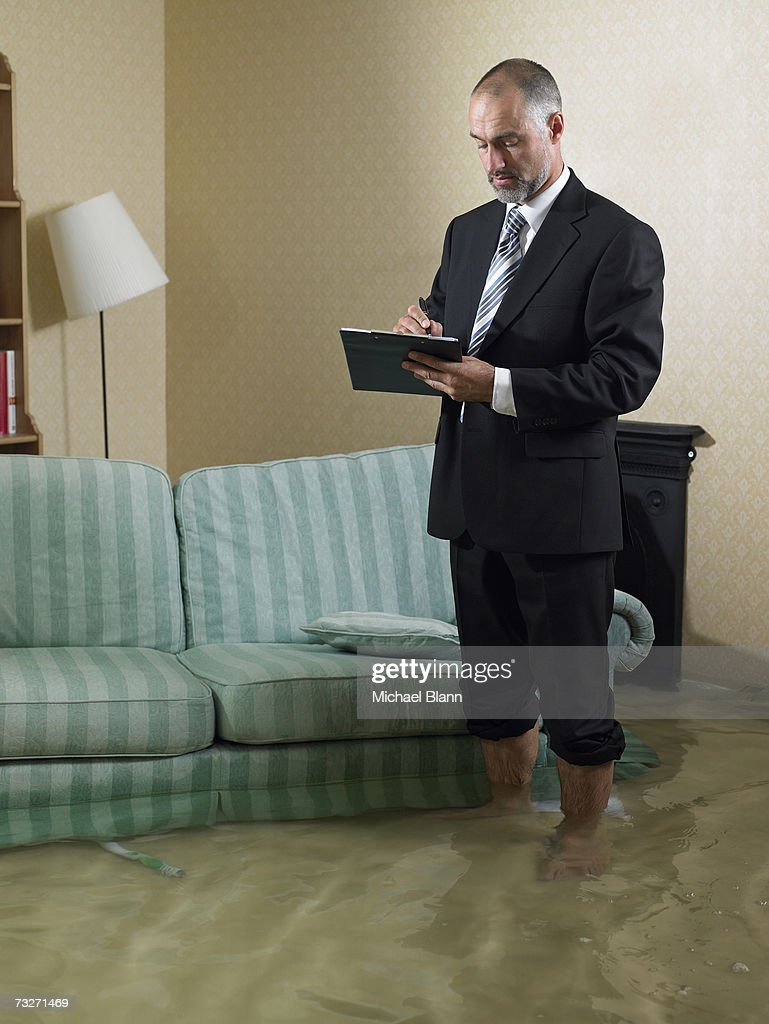 Claims adjuster standing in flooded living room : Stock Photo