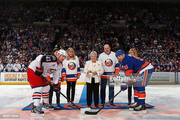 Claire Arbour wife of former New York Islanders head coach Al Arbour is joined by her family for a ceremonial puck drop with Scott Hartnell of the...