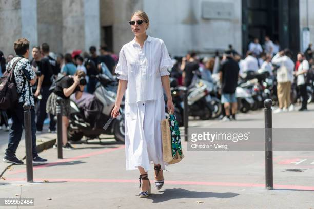Claire Beermann wearing a straw bag white button shirt white skirt outside Rick Owens during Paris Fashion Week Menswear Spring/Summer 2018 on June...