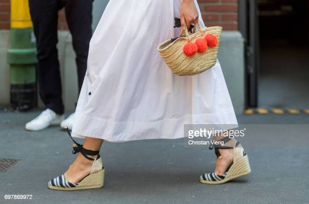 Claire Beermann wearing a white skirt straw bag is seen outside Fendi during Milan Men's Fashion Week Spring/Summer 2018 on June 19 2017 in Milan...