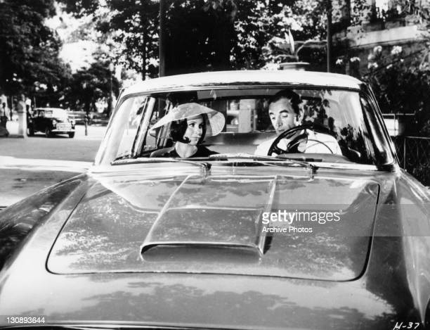 Claire Bloom and Charles Aznavour in the car together in a scene from the film 'High Infidelity', 1964.