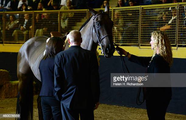 Claire Davis' horse trainer Rebecca Johnson right holds the reins of Claire's horse Graphite as her parents Desiree and Michael Davis left get...