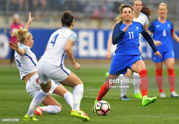 Claire Lavogez of France tries to play the ball past Steph Houghton and Lucy Bronze of England during the SheBelieves Cup at Talen Energy Stadium on...