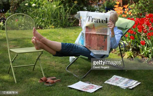 Claire Rogers who is the photographer's wife reads the travel pages on April 12 2020 in Northampton United Kingdom Public Easter events have been...