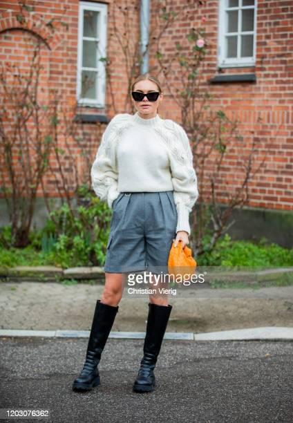 Claire Rose Cliteur wearing grey shorts, knit, orange Bottega bag, black boots seen outside By Malene Birger during Copenhagen Fashion Week...